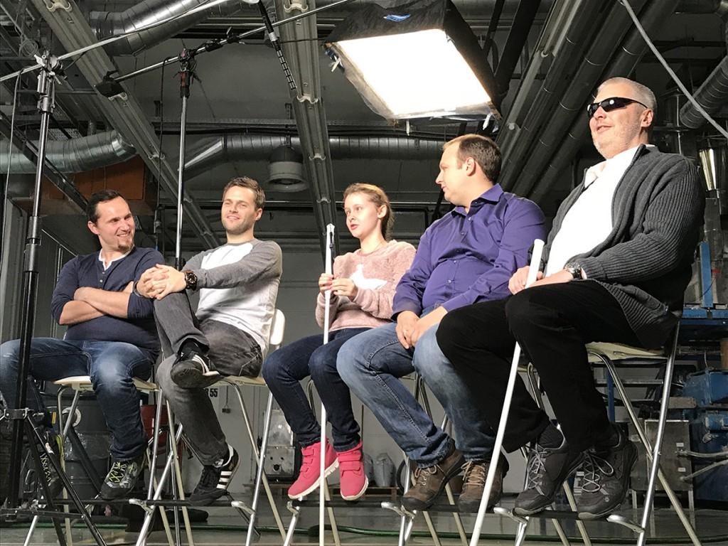 5 Leute aus dem Werbevideo zu SAM sitzen im Halbkreis auf Klappsesseln. Sie sind gut gelaunt. 2 von ihnen haben den Blindenstock SAM in der Hand.