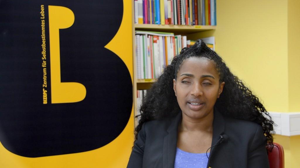 Yetnebersh Nigussi im BIZEPS-Interview. Im Hintergrund ein BIZEPS Banner und ein Teil der Bibliothek.