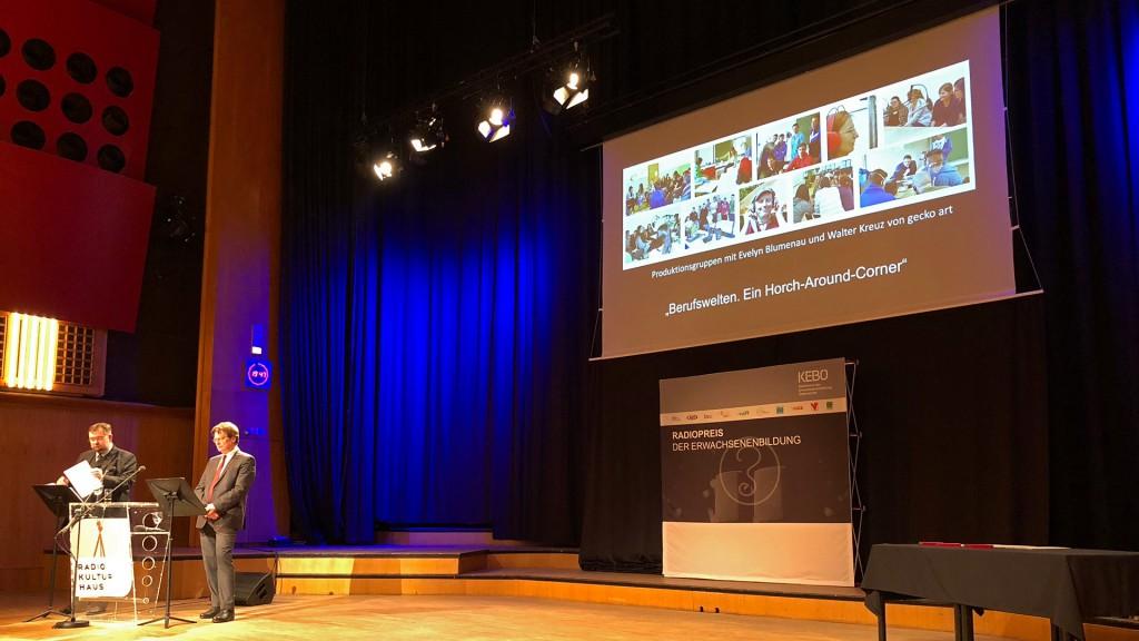 Blick auf die große Bühne mit Parkettboden. Links im Eck sieht man 2 Moderatoren, im Hintergrund als Präsentation groß die Vorstellung der Sendung Berufsbilder