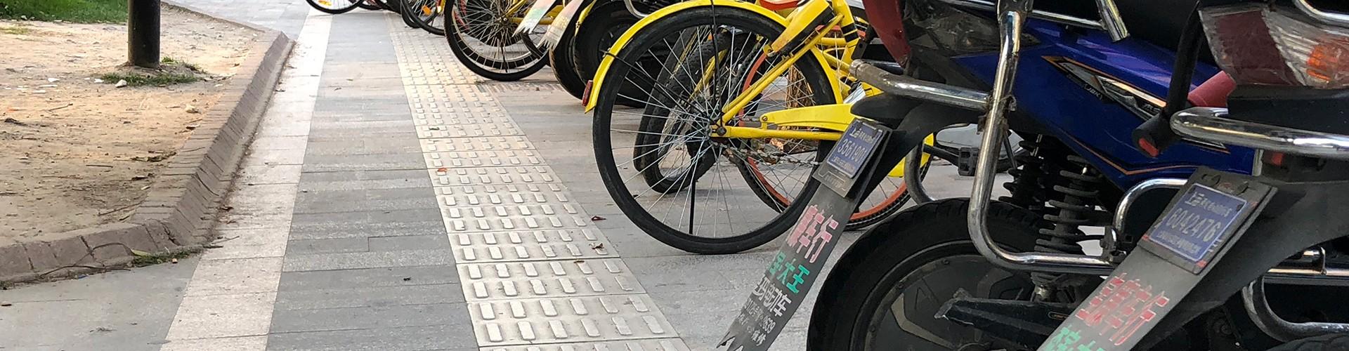Das taktile Leitsystem am Gehsteig wird von ganz vielen Mopeds und gelben Fahrrädern blockiert. Auch zum vorbei gehen bleibt nur noch weniger als 1 Meter Platz.