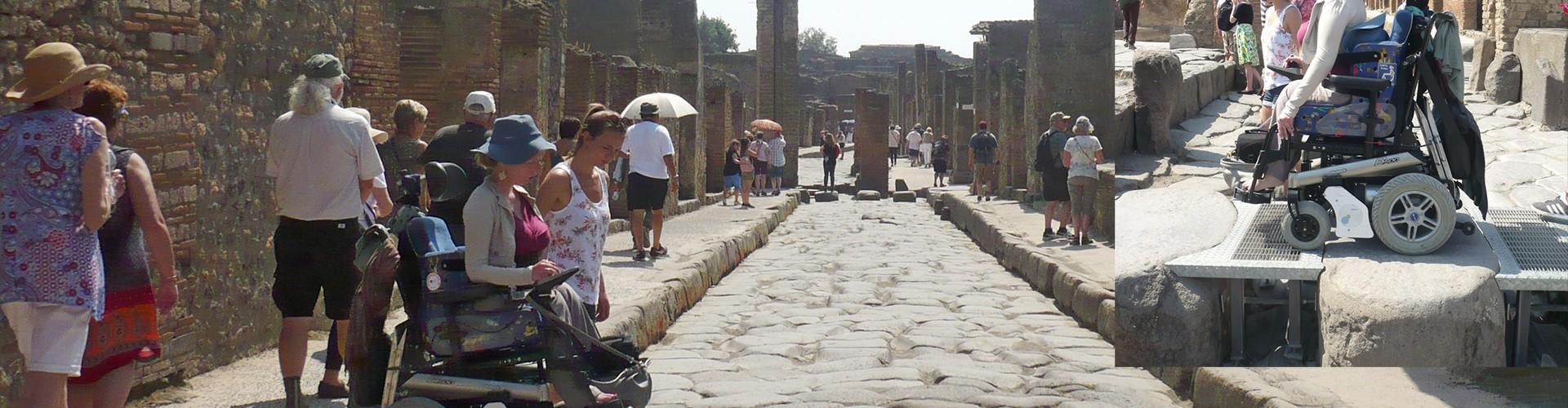 Man sieht eine Frau im Elektrorollstuhl von in einer Ruinenstadt von links nach rechts über eine Art Steg mit großen Steinen fahren. Damit das möglich ist sind die großen Zwischenräume mit Metallgittern ausgefüllt. Rechts oben ein zweites Foto dass die Rampe aus der Nähe zeigt.