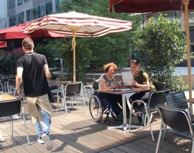 Zwei Frauen - eine davon Rollstuhlnutzerin - in einem Gastgarten