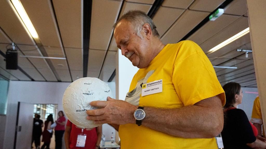 Ein sehbehinderter Mann ertastet auf einem 3-D-Modell des Mondes dessen Oberfläche mit Kratern und Gebirgen