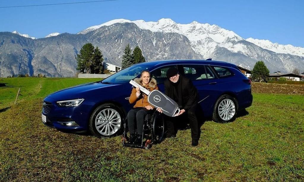 Vertreter von Opel übergibt Kira Grünberg einen blauen Opel