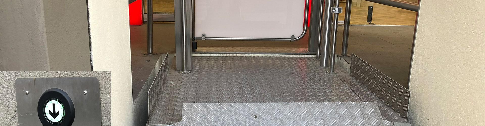 Frontalansicht eines Rollstuhlhubliftes im Freien bei einer Sparfiliale der mit Euroschlüssel selbstständig zu bedienen ist.