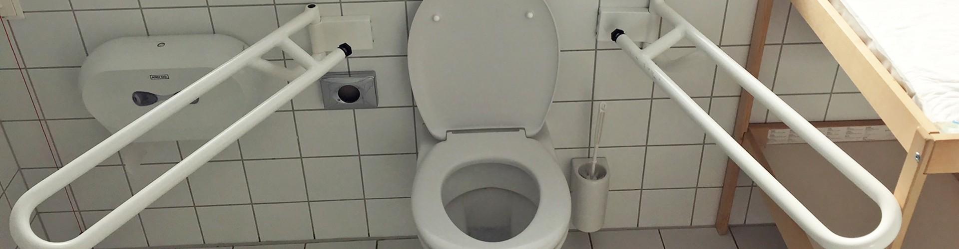 Frontalansicht auf eine barrrierefreie Toilette bei der die seitlichen Haltegriffe nicht von oben nach unten klappen sondern vom Toilettensitz nach außen schwenken.