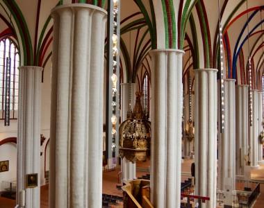 Innenansicht der Nikolaikirche in Berlin von oben. Man sieht viele Säulen und die grün, rot und blauen Verzierungen an der Decke.