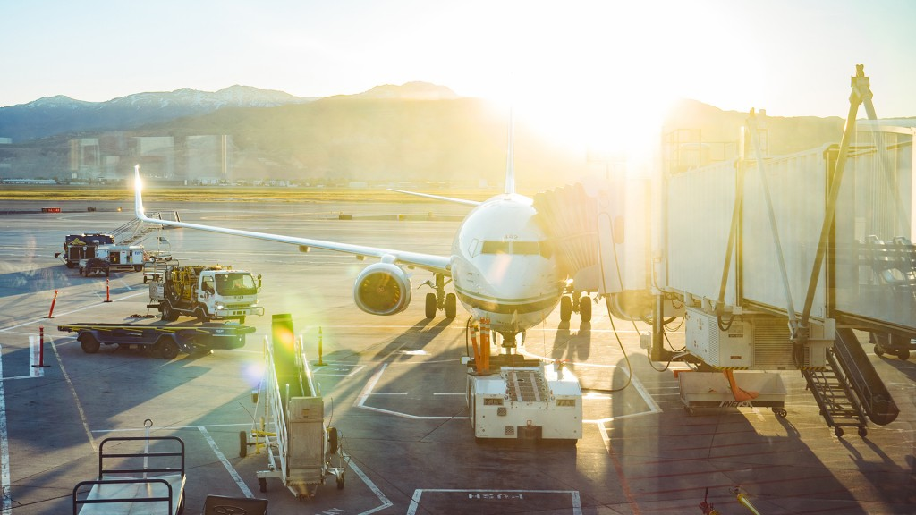 Die Sonne scheint uns entgegen, man sieht ein Flugzeug von vorne, dass an einer Fluggastbrücke angedockt ist. Links davon sieht man auch das Vorfeld und Fahrzeuge zur Beladung des Flugzeuges.