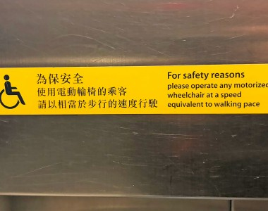 Ein Aufkleber in einem Aufzug in Hong Kong: For safety reasons please operate any motorized wheelchair at a speed equivalent to walking pace