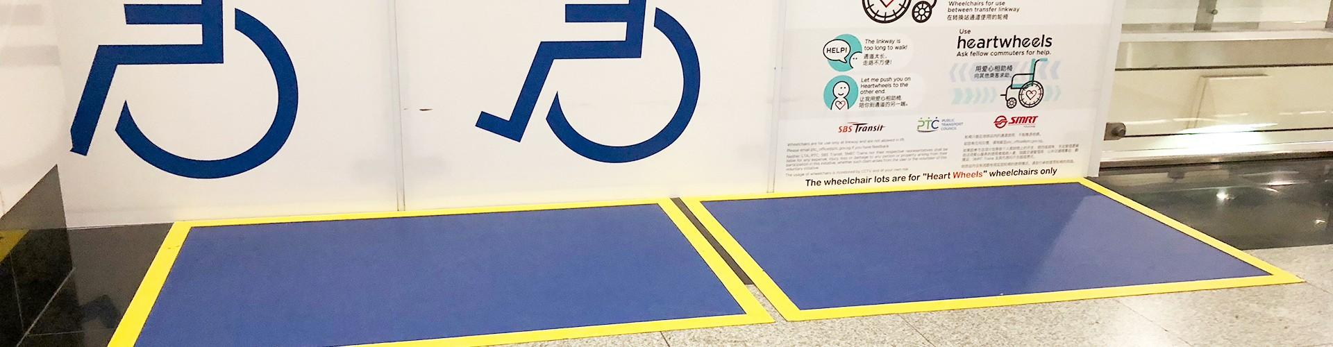 In einer U-Bahn-Station. Am Boden Aufkleber Priority Queue für Rollstuhlfahrer, ältere Personen, Verletzte, Schwangere und mit Kinderwagen. Dahinter 2 blau markierte Abstellflächen. Dahint an der Glaswand mit großen Hinweisen Rollstuhl und heartwheels Projekterklärung.
