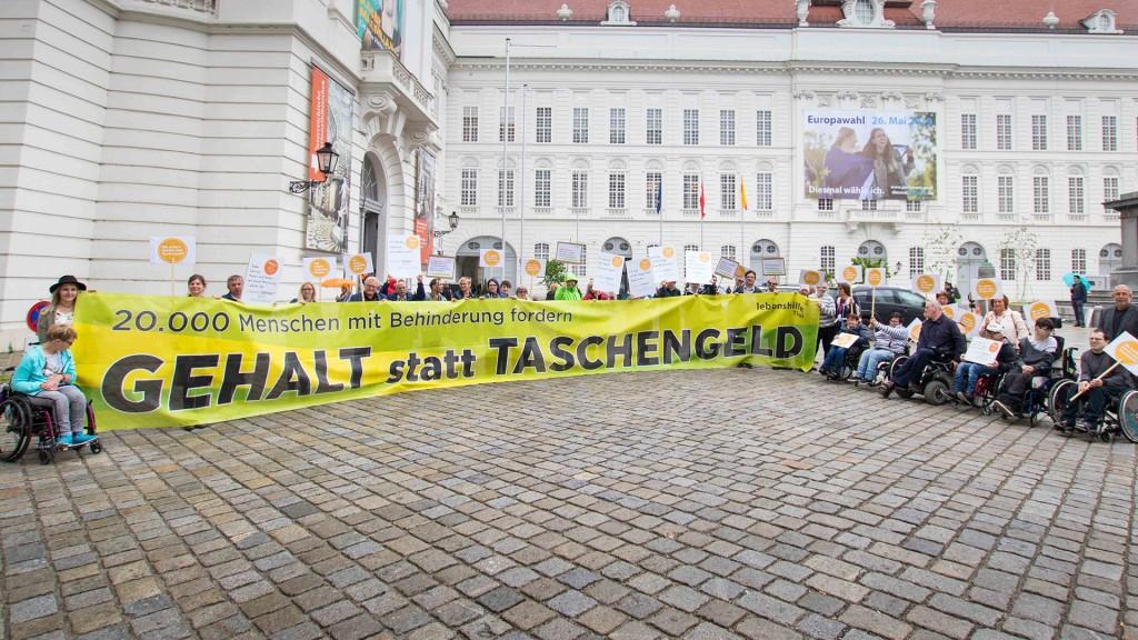 Gruppe von Menschen mit dem Schild: 20.000 Menschen mit Behinderung fordern - Gehalt statt Taschengeld