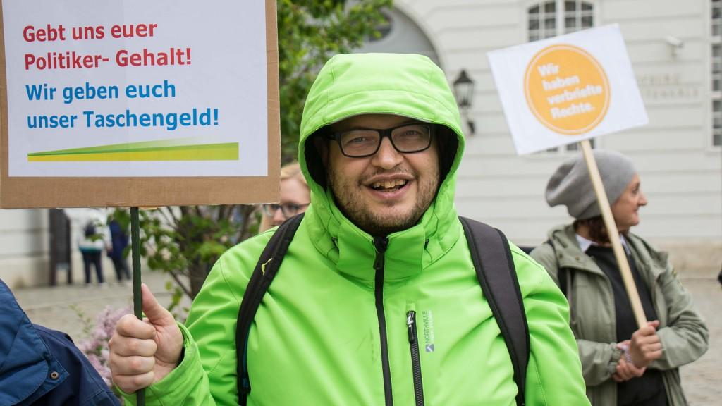 Mann hält Schild: Gebt uns euer Politiker-Gehalt! Wir geben euch unser Taschengeld!