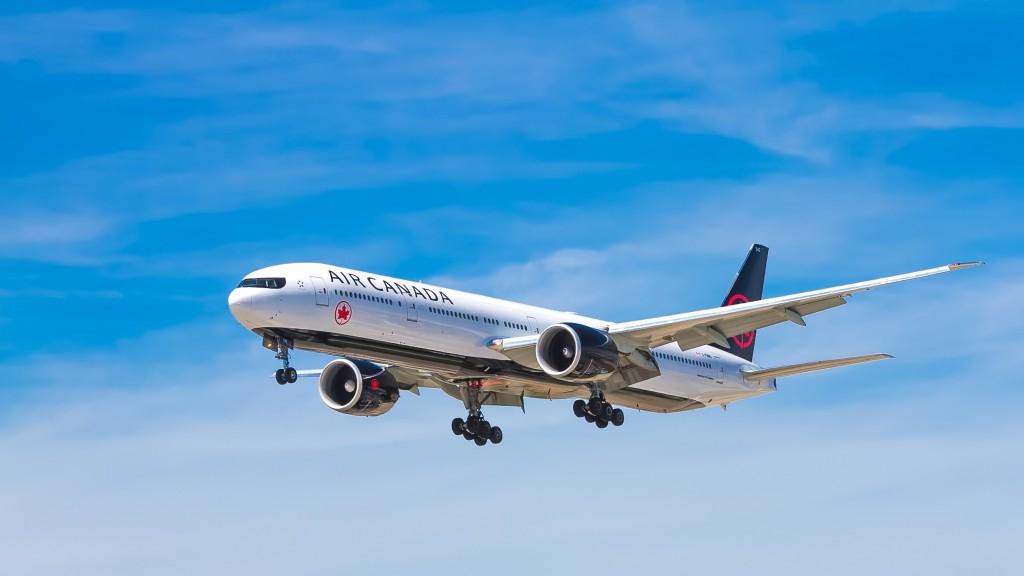 Ein Flugzeug mit Beschriftung Air Canada fliegt von rechts nach links. Im Hintergrund sind man blauen Himmel mit leichter Bewölkung.