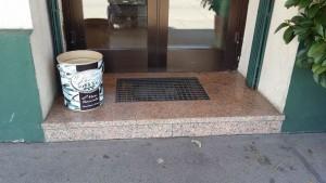 Eine Eingangssituation zu einem Geschäft. Eine ca. 10 cm hohe Stufe zu einem Plateau, auf ihm steht auch noch eine große leere Haselnuss Krem Dose. Dahinter die Tür.