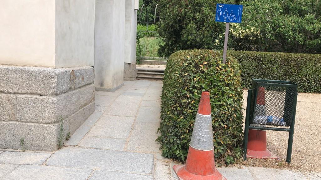 Ein Steinweg führt einer Hausmauer entlang zu 3 Stufen. Dort soll laut Hinweistafel auch die barrierefreie Toilette sein.