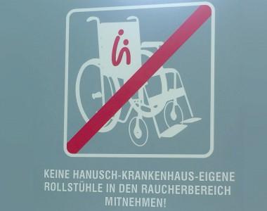 Ein durchgestrichenes Rollstuhlsymbol, darunter der Text KEINE HANUSCH-KRANKENHAUS-EIGENE ROLLSTÜHLE IN DEN RAUCHERBEREICH MITNEHMEN!