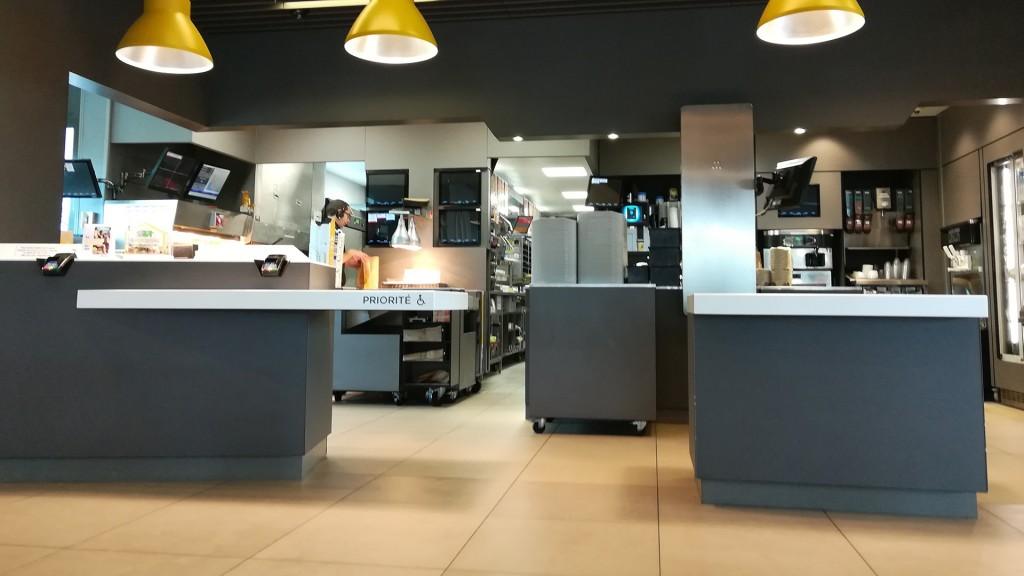 Beim Essensübergabeschalter einer McDonald's Filiale ist rechts außen ein abgesenkter Tischbereich mit der Aufschrift Priorité und einem Rollstuhlsymbol.