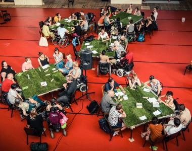 TeilnehmerInnen sitzen an Tischen mit Grasoberfläche