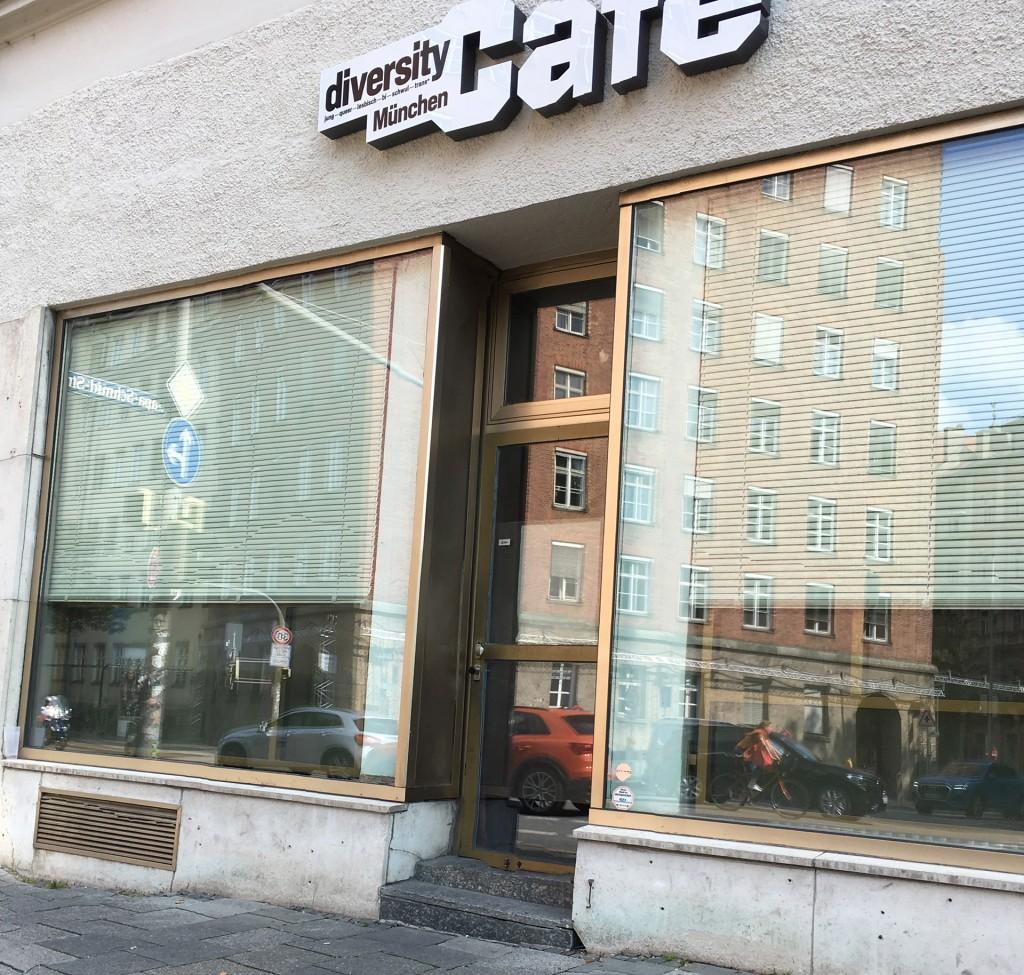 Ein Geschäftseingang zum diversity Café München. 2 Stufen führen hinein.