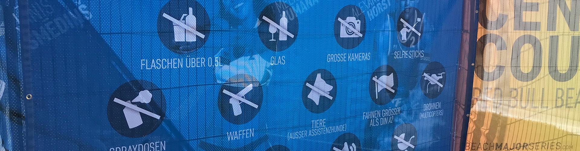 Plakat mit Text: Verbotene Gegenstände im Veranstaltungsgelände. Dann 15 Verbote unter anderem Tiere, ausgenommen Assistenzhunde)