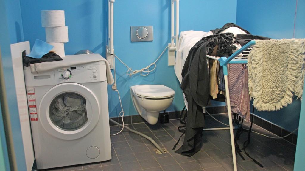 Behindertentoilette vollgeräumt mit einem Wäscheständer rechts, einer Waschmaschine links und einen Schlauch mit Loch im Boden vor dem Toilettensitz.