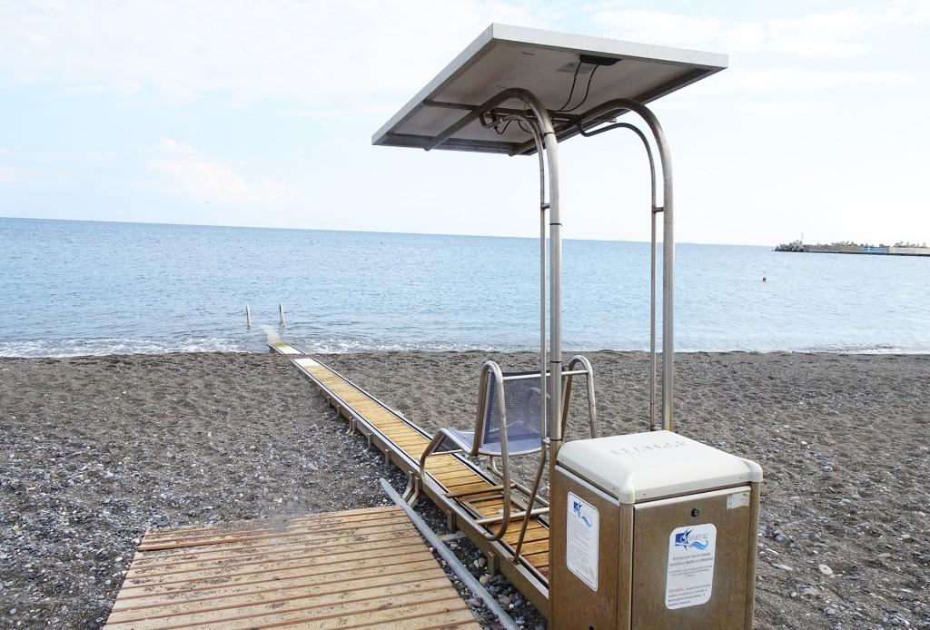 Wir sind am Strand. Ein Holzsteg führ bis zu einem überdachten Sitz auf Schienen der bis ins Meer geschoben werden kann.