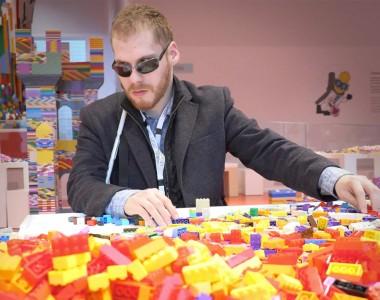 Matthew Shifrin hat einen Haufen Legosteine vor sich, den Langstock unter dem Arm eingeklemmt und sortiert Legosteine.