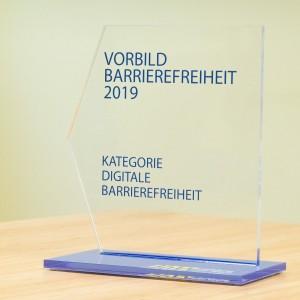 Ein transparenter Pokal mit blauer Bodenplatte, Text: Vorbild Barrierefreiheit 2019 Kategorie Digitale Barrierefreiheit