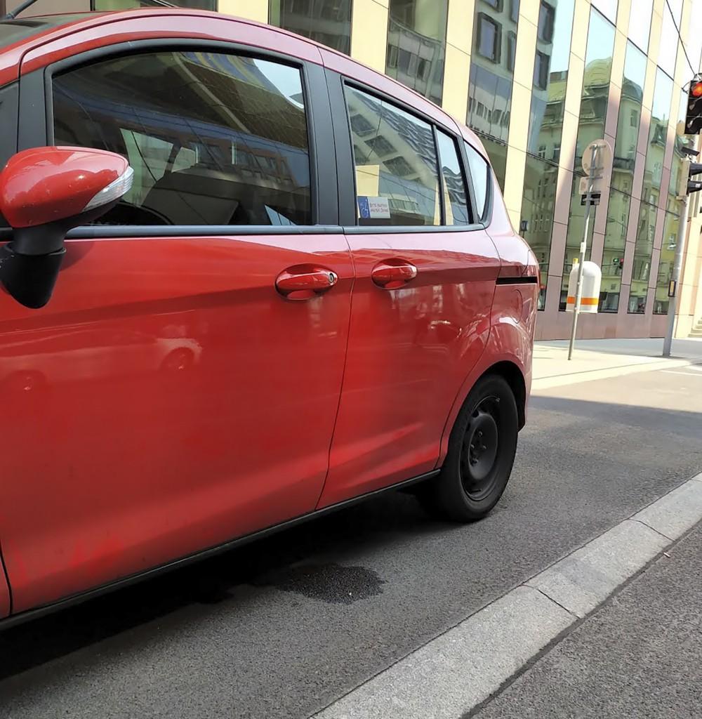 Ein rotes Auto steht in unsere Richtung auf einem Behindertenparkplatz. Rechts vom Auto ist der Gehsteig, links die Fahrbahn. Vom Parkplatz zur Fahrbahn ist eine Abschrägung.