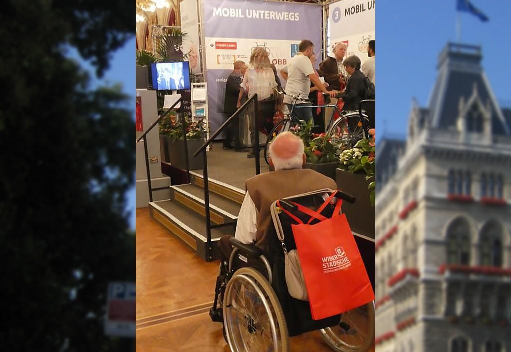Ein Rollstuhlfahrer steht vor einem Messepodest. Auf dem Podest stehen Menschen mit Fahrrädern und dem Schriftzug Mobil unterwegs. Es gibt nur Stufen.