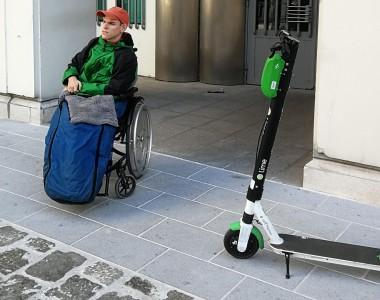 Ein Mann im Rollstuhl steht auf einem glatten Betonstreifen. Man sieht im Vordergrund auch noch Pflastersteine. Am glaten Beton verstellt ein E-Scooter den Weg. Im Hintergrund das Schild Bundesministirium Inneres
