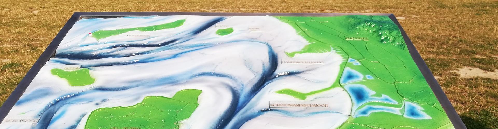 Man schaut auf einen Lageplan der nordfriesischen Inseln in Deutschland. Der Plan ist taktil ertastbar und man kann so die Lage der Inseln und Küste spüren. Im Hintergrund sieht man das Meer.