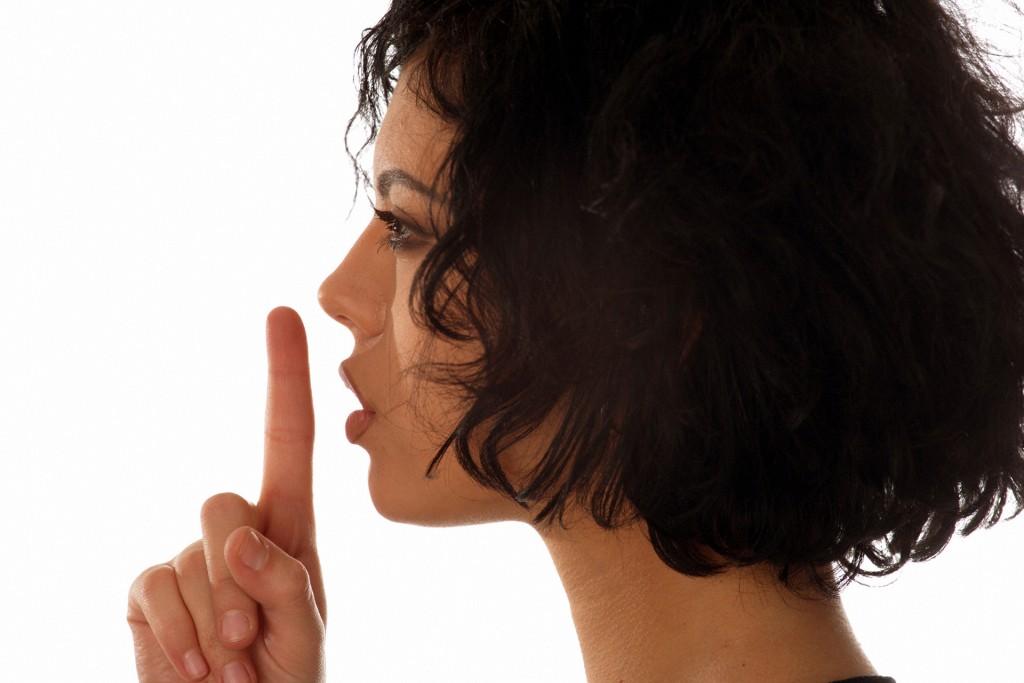Bitte leise - Frau hält Zeigefinder vor den Mund