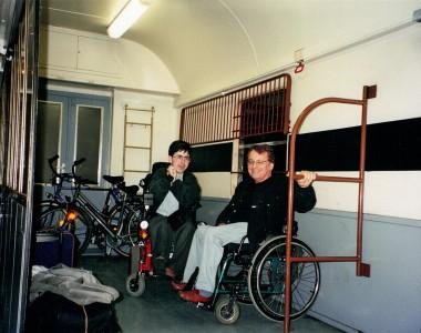 2 Rollstuhlfahrer in einem alten Gepäckwagen. Rundherum Fahrräder und Koffer.