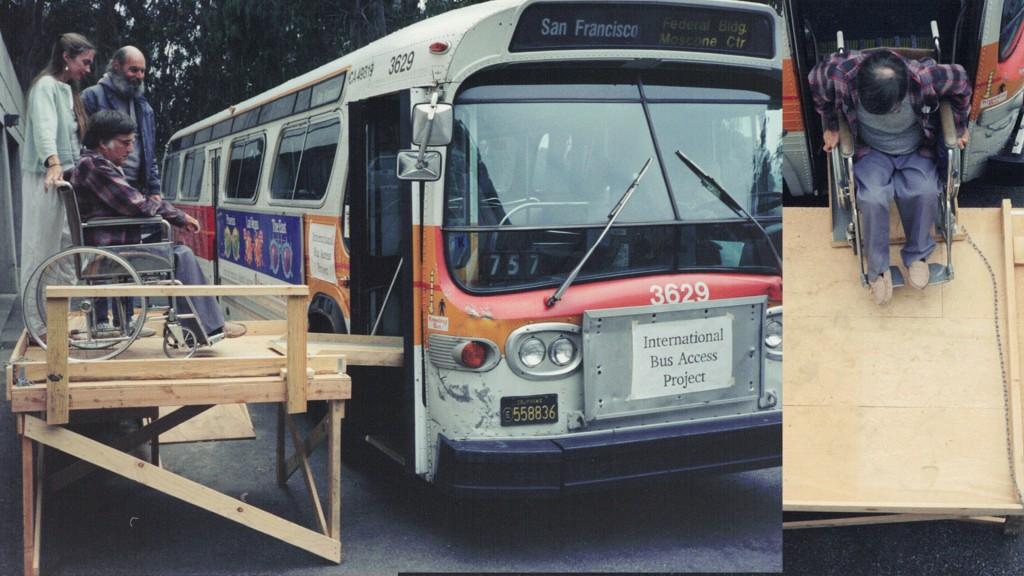 Ein alter Bus in San Francisco. Ein Rollstuhlfahrer mit 2 anderen stehenden Personen ist auf einem Holzgerüst um in den Bus fahren zu können. Am Bus steht International Bus Access Project