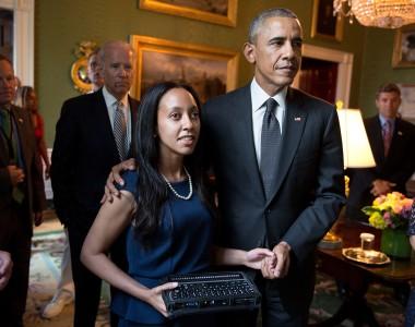 Haben Girma steht neben Barack Obama und hält einen mobilen Braillecomputer in der Hand. Im Hintergrund andere Personen.