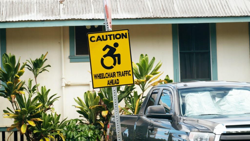 Ein gelbes Straßenschild darauf der Text Caution Rollstuhlsymbol Wheelchair traffic ahead