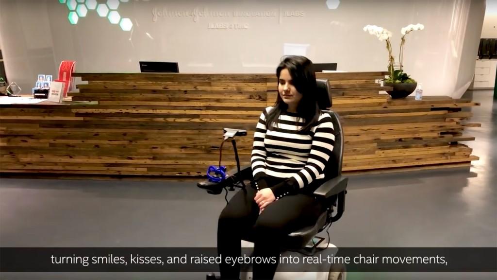 Eine Frau im Elektrorollstuhl. Man sieht vor ihr eine Kamera. Darunter der Text turning smiles, kisses, and raised eyebrows into real-time chair movements