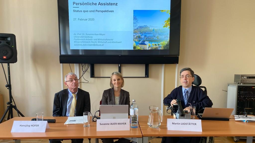 Hansjörg Hofer (Behindertenanwalt), Susanne Auer-Mayer (Universität Salzburg) und Martin Ladstätter (Monitoringausschuss) sitzen an einem Tisch vor eine Präsentation auf der steht Persönliche Assistenz und schauen in die Kamera