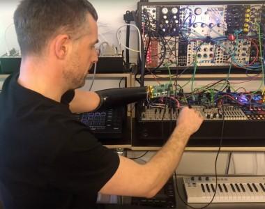 Ein Man mit Armprothese sitzt vor sehr vielen elektronischen Geräten mit Kabeln.