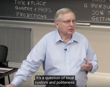 Man steht vor eine Kreidetafel und spricht. Darunter Untertitel It is a question of local custom and politeness.