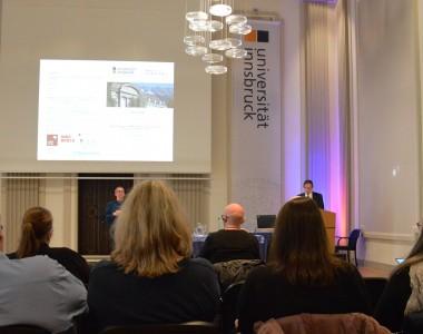 Menschen sitzen und schauen auf eine Vortragspräsentation. Links und rechts Banner mit Aufschrift Universität Innsbruck