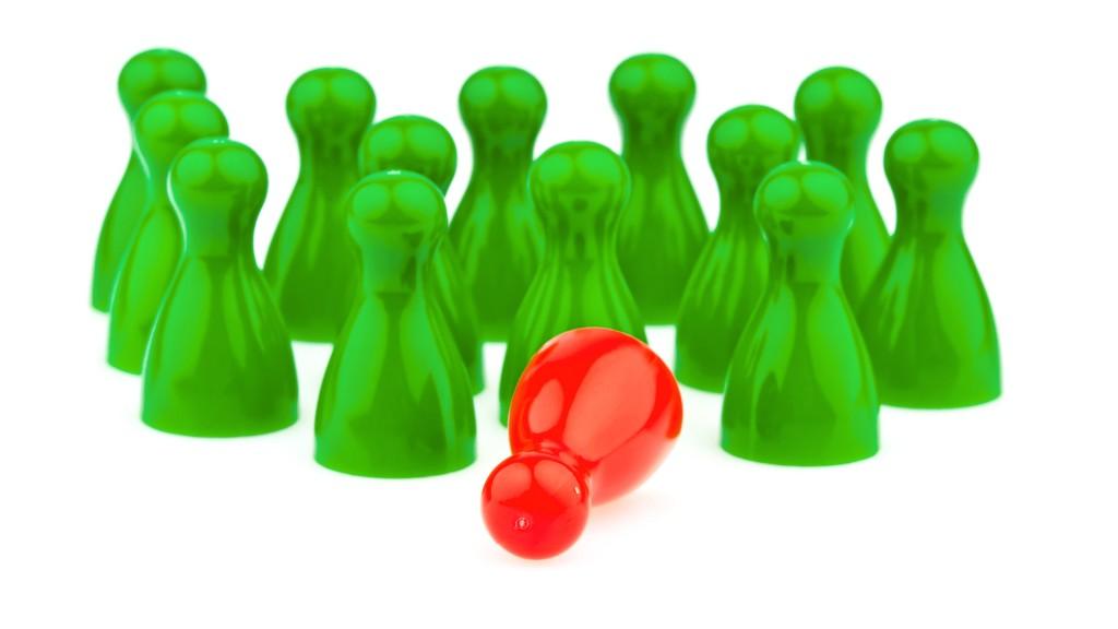 Symbolbild für Aussonderung: Viele grüne Spielfiguren und eine umgefallene rote Spielfigur