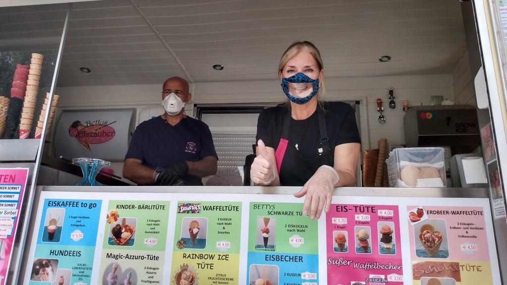 Ein Man und eine Frau stehen in einem Eisstand. und schauen heraus. Die Frau hat einen Mund-Nasen-Schutz mit transparentem Mundteil. Sie lächelt und zeigt Daumen nach oben.