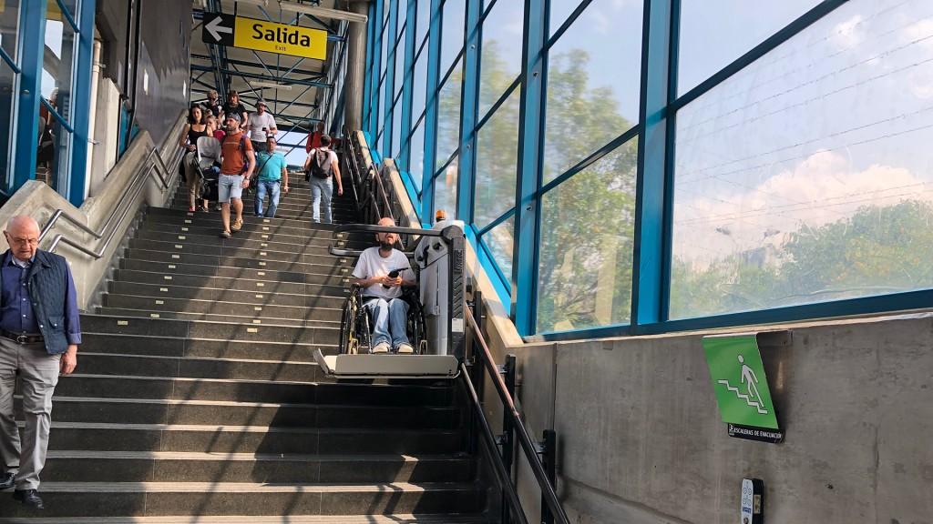 Eine Person im Rollstuhl fährt auf einem Treppenlift Stiegen in einer U-Bahnstation hinunter. Er fährt den Betrachter zu. Rechts davon sind große Glasfenster und viel Licht scheint herein.