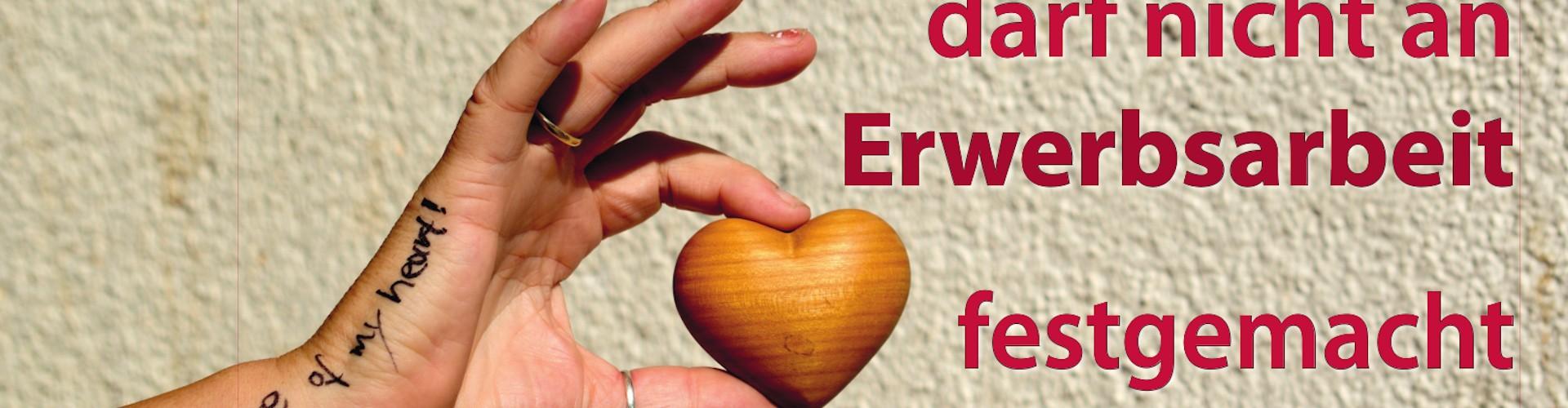 Eine Hand mit einem Holzherz zwischen Zeigefinger und Daumen. Auf der Hand der Text Take care of my heart! Daneben der Text: Die Würde eines Menschen darf nicht an Erwerbsarbeit festgemacht werden