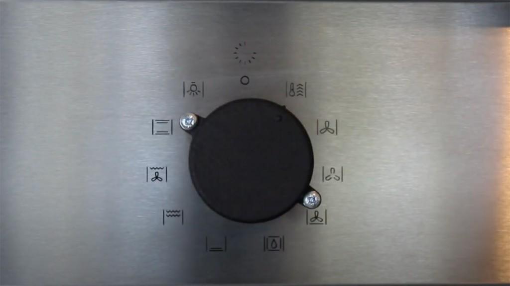 Ein schwarzer Drehknopf mit 2 ertastbaren Ausbuchtungen auf einem Edelstahlhintergrund mit Symbolen eines Herdes.