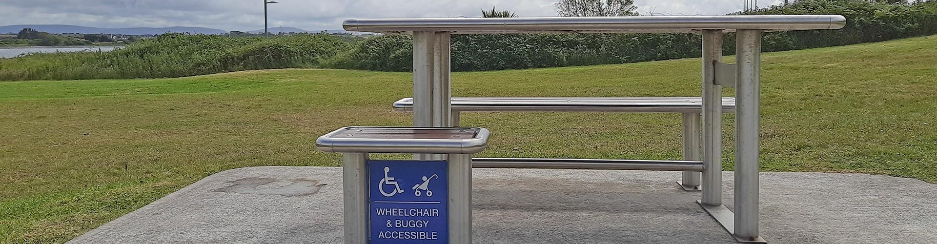 Ein Picknicktisch aus Edelstahl von der Seite. Man sieht dass nur auf einer Seite eine durchgehende Sitzbank ist, auf der anderen Seite ist ein kleiner Sitz, daneben Freiraum. Unter dem Sitz ein Schild Wheelchair and Buggy accessible