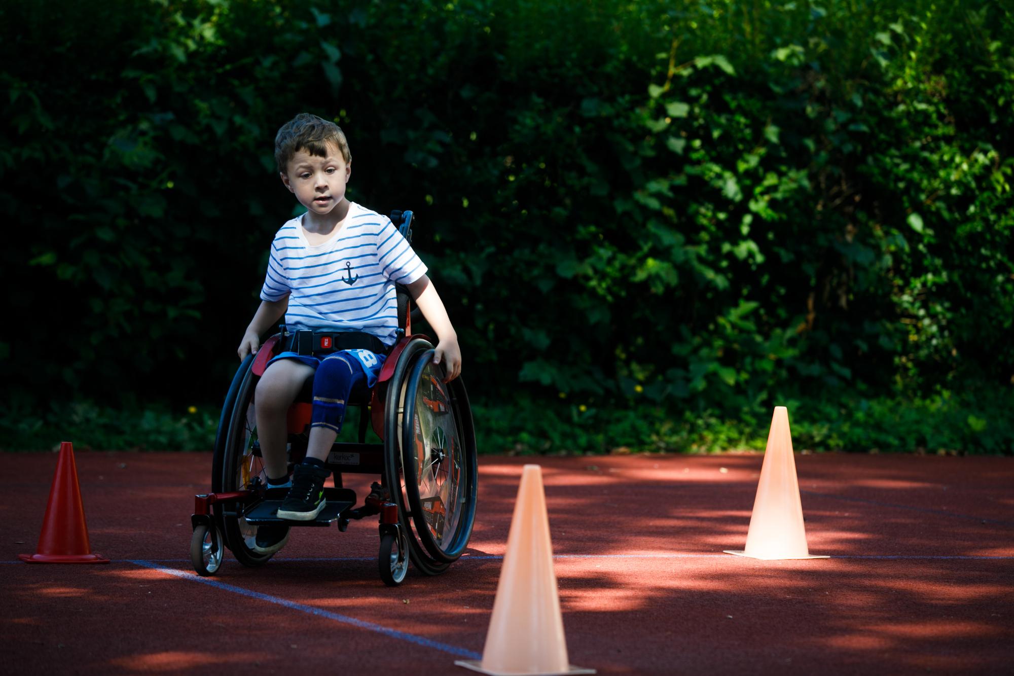 Kind im Rollstuhl fährt zwischen Kegeln Slalom