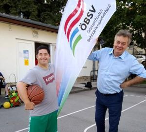 Sportminister Kogler mit einem Sportler im Rollstuhl und der ÖBSV-Fahne